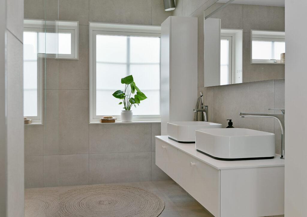 Bild på ett badrum med dubbla handfat och stor spegel