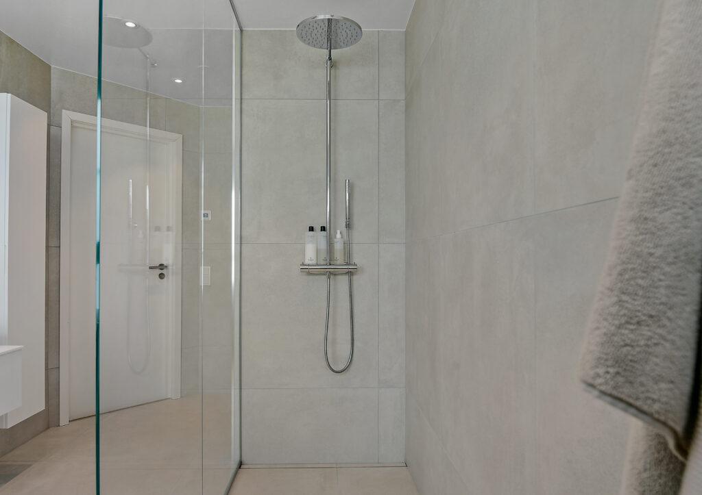 Bild på en dusch i ett badrum med glasvägg och takdusch