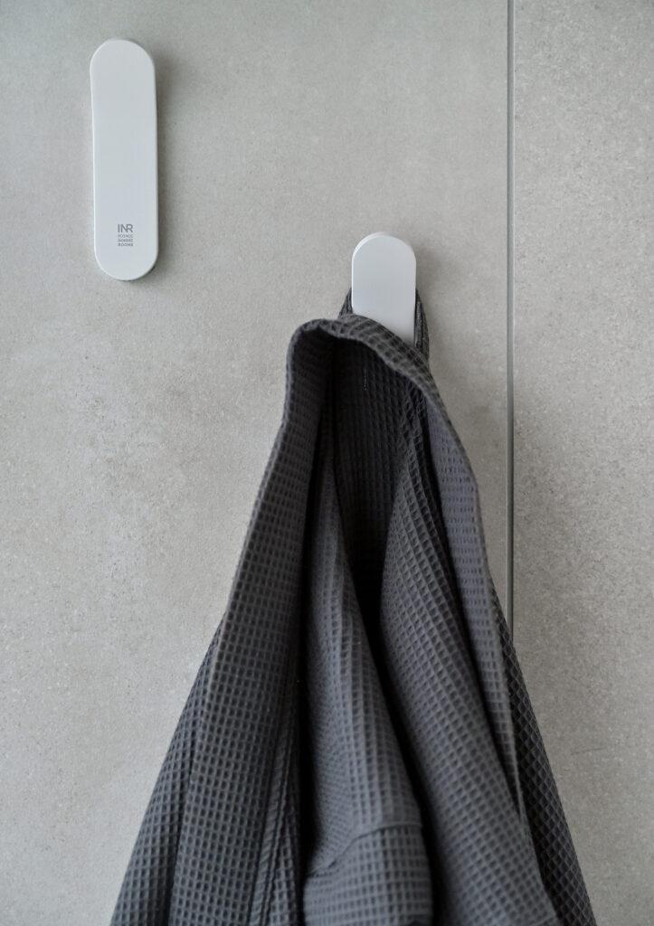 2 krokar i ett badrum. På ena kroken hänger en grå morgonrock.